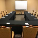 U shaped table with chairs and projector screen